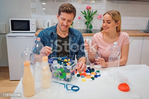 1137022282 istock photo Protect the environment. Aware young couple recycling empty plastic bottles and lids while sitting at the table with other waste at home 1137022258