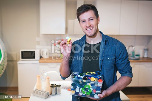 1137022221 istock photo Protect the environment. Plastic lids prepared for recycling. Young smiling man holding recycling container filled with bottles lids on kitchen background 1137022219