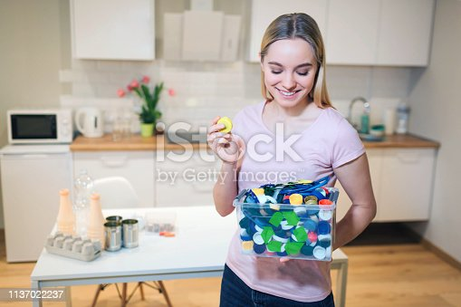 1137022221 istock photo Protect the environment. Plastic lids prepared for recycling. Young smiling woman holding recycling container filled with bottles lids on kitchen background 1137022237