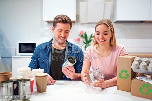 1137022221 istock photo Protect the environment. Young couple recycling metal tin can and glass while sitting at the table with other waste at home 1137022271
