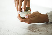 Close up of female hands opening a small round jar of cream by twisting the lid before using it to moisturize skin.