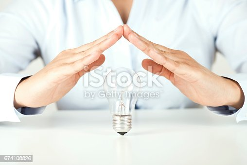 Businessperson is making a roof with hands to protect a light bulb representing an new idea.