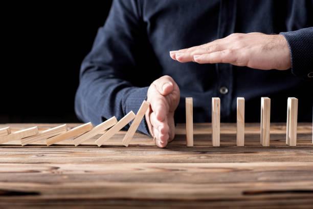 protecting assets from domino effect. stop loss concept. - fare la guardia foto e immagini stock