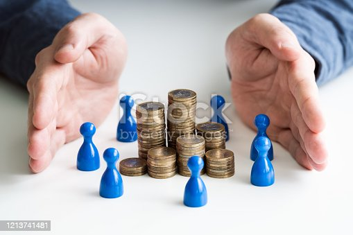 Businessperson's Hand Protecting Blue Human Figures Surrounding Stacked Golden Coins Over Desk
