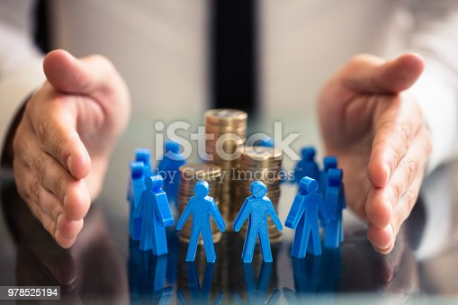 istock Protecting Blue Human Figures Surrounding Stacked Coins 978525194