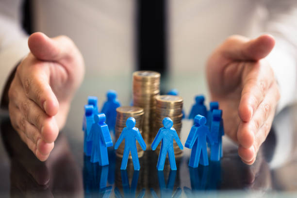 Protecting Blue Human Figures Surrounding Stacked Coins stock photo