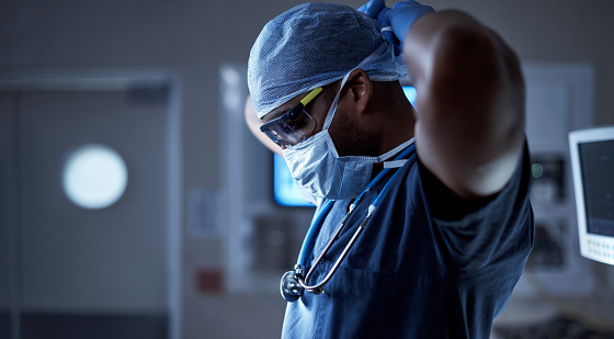 Shot of a surgeon putting on his surgical mask in preparation for a surgery