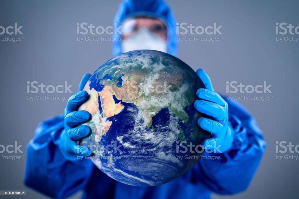 Protecting world from Coronavirus COVID 19 novel corona outbreak Doctor wearing highly protective suit and holding globe in her hands. Globe link: https://visibleearth.nasa.gov/images/2181/the-blue-marble/2182w Adult Stock Photo