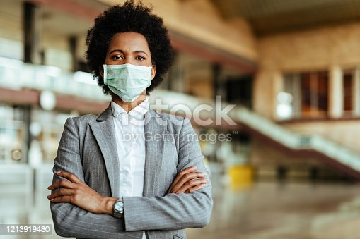 Portrait of African American woman wearing protective mask while standing with arms crossed at the airport during virus epidemic.