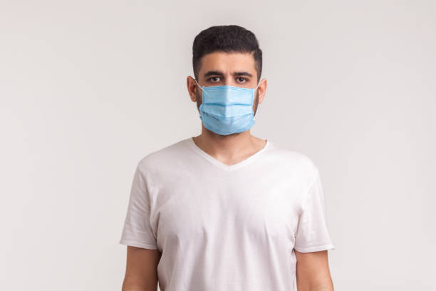 Protection against contagious disease, coronavirus. Man wearing hygienic mask to prevent infection, airborne respiratory illness stock photo