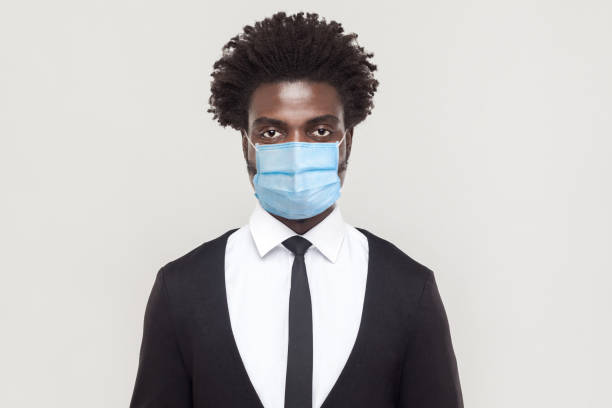 protection against contagious disease, coronavirus. man wearing hygienic mask to prevent infection, airborne respiratory illness such as flu, covid-19. - businessman covid mask foto e immagini stock