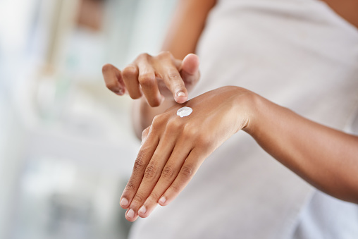 Cropped shot of a woman applying moisturiser to her hands during her morning beauty routine