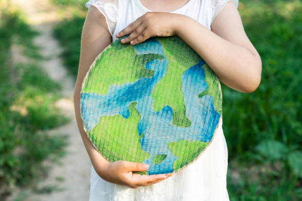 protection and love of earth. little girl holding planet in hands against green spring background. earth day holiday concept. - earth day stock pictures, royalty-free photos & images