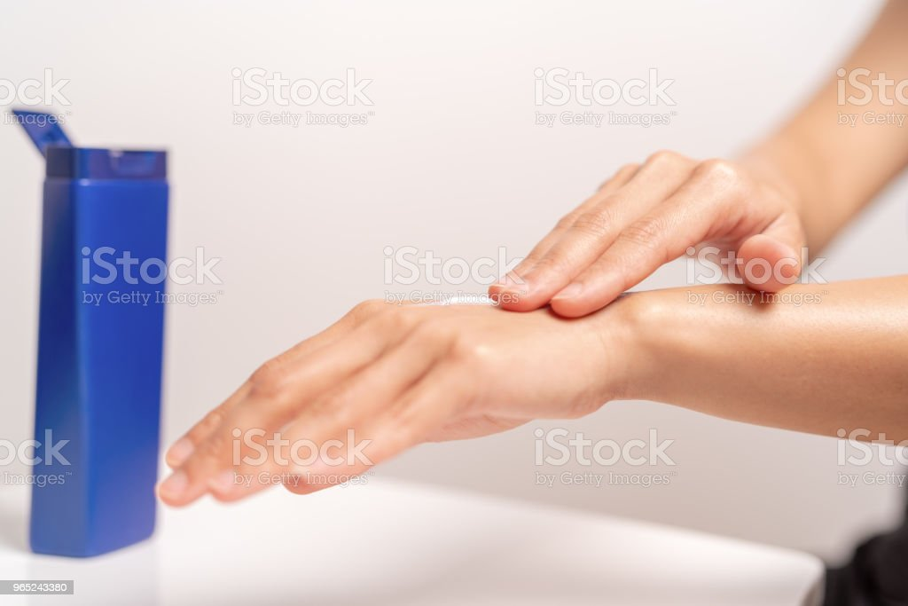 UV Protection Body Lotion Skin Care Apply. women hands holding UV protection body cream bottle. Beauty And Body Care Concept zbiór zdjęć royalty-free