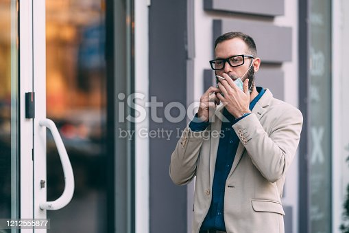 Businessman with mask during COVID-19 pandemic smoking at the street
