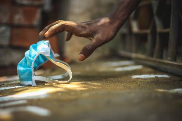 schutz maske auf männer hand gegen corona-virus, infektion sanatosie-konzept. armutskranke nehmen blaue gesichtsmaske auf der hand - armut stock-fotos und bilder