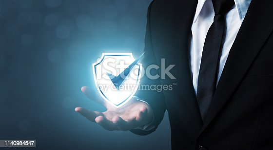 938535190istockphoto Protection network security computer and safe your data concept, Businessman holding shield protect icon 1140984547