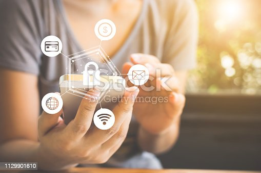 istock Protection network security smartphone and safe your data concept. Close up view hand of asian woman using mobile phone 1129901610