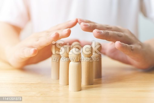 istock Protection people health and insurance concept. Hand shield protect wooden human on table 1141201373
