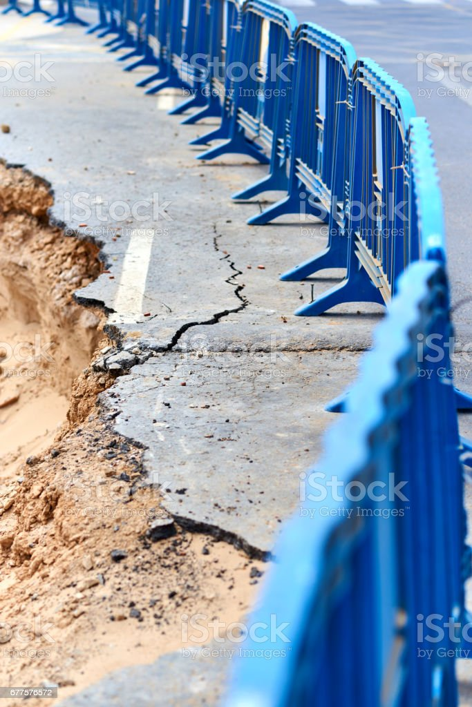 Protective barrier and destroyed asphalt road royalty-free stock photo