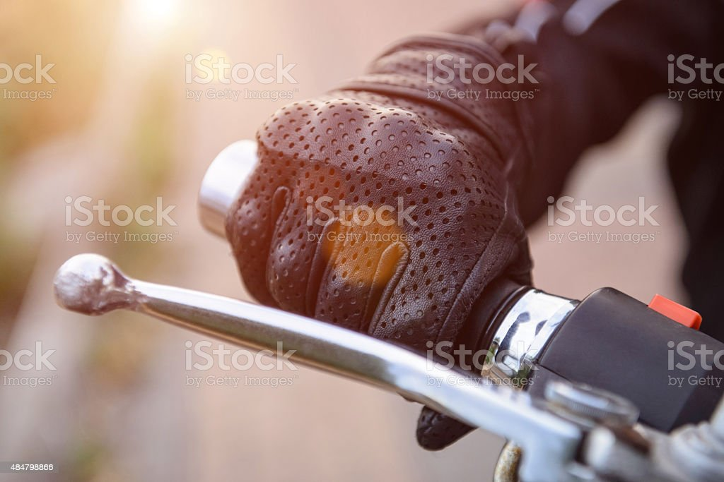 protective biker gloves on a motorcycle wheel stock photo