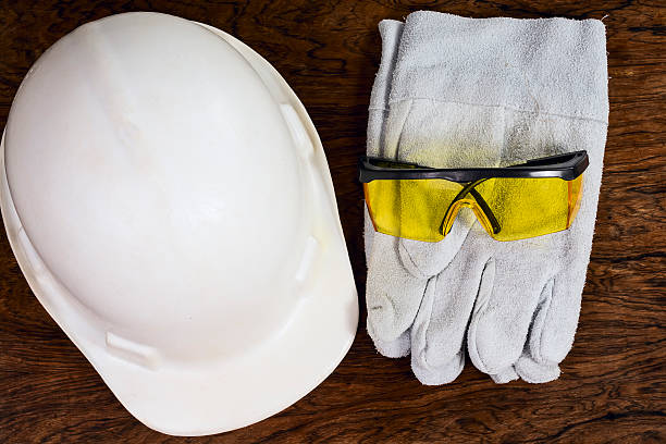 Protective equipments. A pair of gloves, protective goggles and a helmet, on a wooden surface. It suggests construction and industry. individual event stock pictures, royalty-free photos & images
