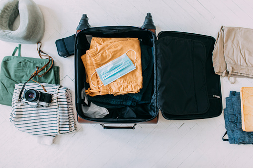 Protective face mask packed into a suitcase along with clothes and a camera, covid 19 prevention concept.
