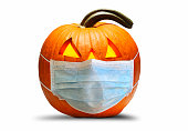 A protective face mask on an illuminated jack o'lantern isolkated on a white background