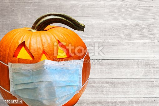 A protective face mask on an illuminated jack o'lantern in front of whitewashed wooden planks.