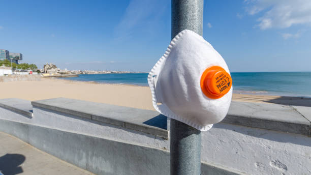 Protective facemask on pole overlooking a public beach in Cascais, Portugal during Coronavirus outbreak stock photo