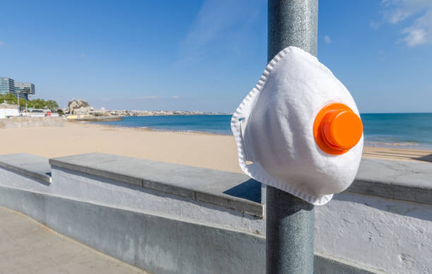 Protective facemask on pole overlooking an empty public beach during the Coronavirus outbreak stock photo