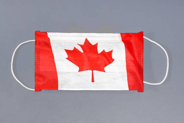 Schutz Gaze Maske mit Flagge von Kanada auf grauem Hintergrund. Medizinische Schutzmaske auf grauem Hintergrund. – Foto