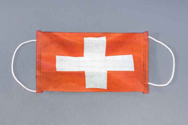 Schutz gaze Maske mit Flagge der Schweiz auf grauem Hintergrund. Medizinische Schutzmaske auf grauem Hintergrund. – Foto