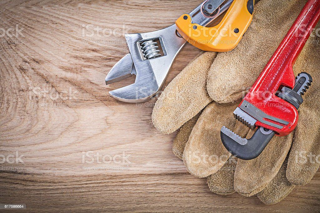 Protective gloves adjustable key monkey wrench pipe cutter on wo stock photo