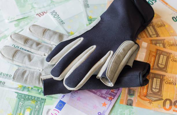 schutzhandschuhe für das segeln vor dem hintergrund der euro-banknoten. - segelhandschuhe stock-fotos und bilder