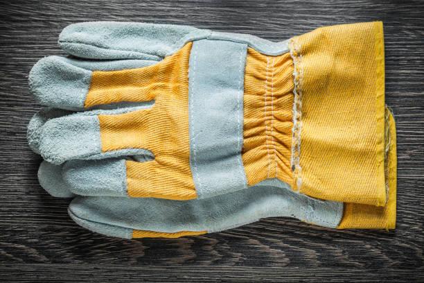 schutzhandschuhe auf holzbrett draufsicht - diy leder stock-fotos und bilder