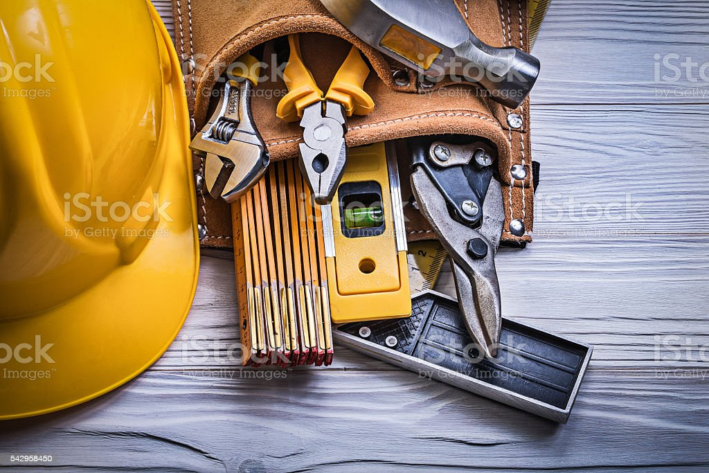 Protective hard hat tool belt on wooden board construction conce stock photo