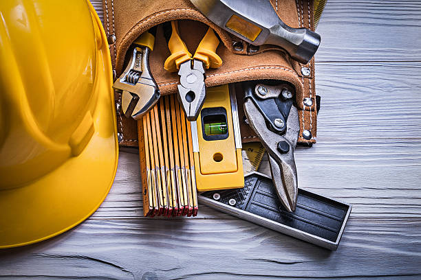 protective hard hat tool belt on wooden board construction conce - tool belt stock photos and pictures