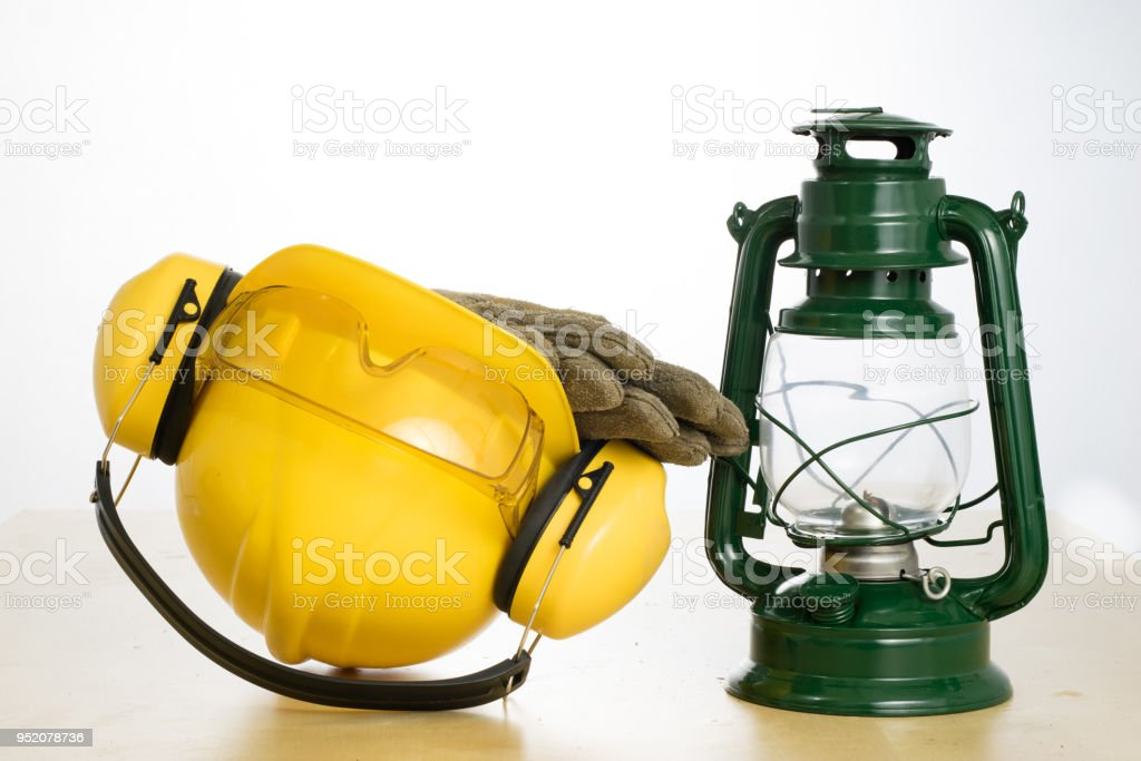 Protective helmet and work boots on a wooden table. Safety and health...