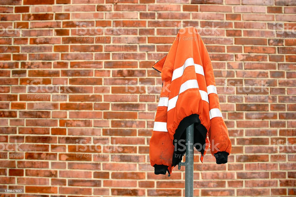 Protective jacket (construction site) in front of a wall stock photo