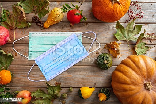 Thanksgiving 2020, coronavirus days, Protective face mask and thanksgiving flatlay on wooden background. COVID 19 spread prevention measure