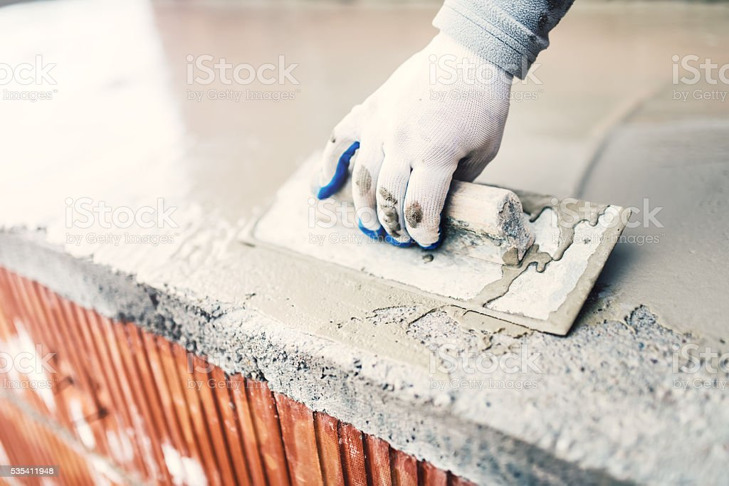 protective material against water on house building. worker waterproofing cement stock photo