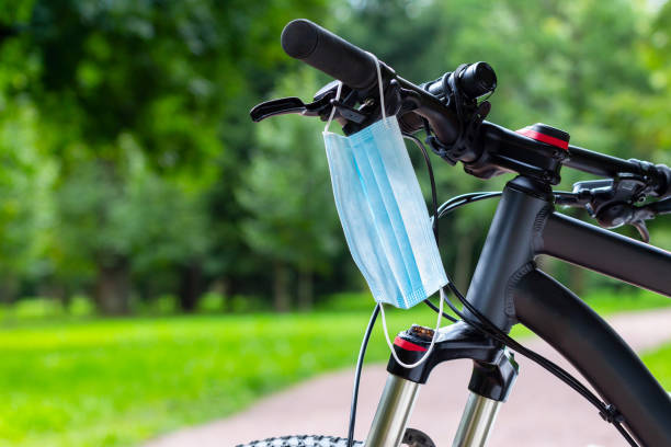 Protective medical face mask hanging on the bike handlebars stock photo
