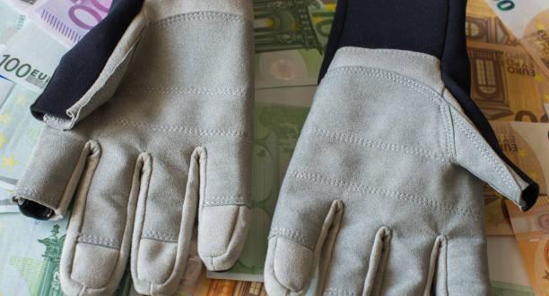 schützende segelhandschuhe vor dem hintergrund der euro-banknoten. - segelhandschuhe stock-fotos und bilder
