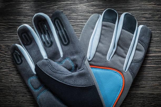 schützende arbeitshandschuhe auf vintage holzbrett - arbeitshandschuhe stock-fotos und bilder