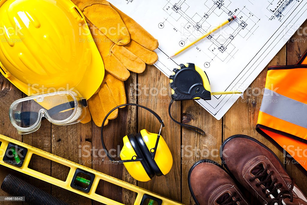 Protective workwear and construction blueprint on wood background stock photo