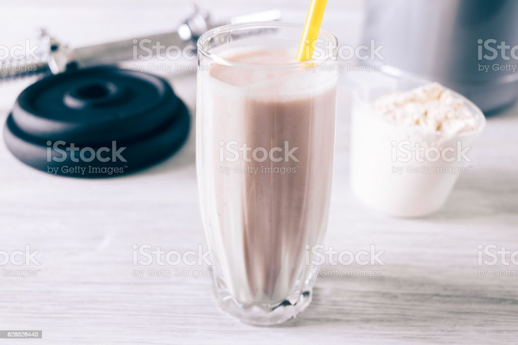 Protein cocktail in a glass with a straw, scoop and dumbbell on a white wooden table stock photo