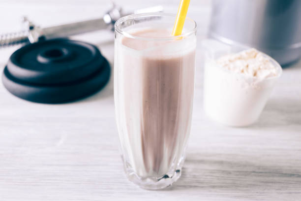 Protein cocktail in a glass with a straw, scoop and dumbbell on a white wooden table Protein cocktail in a glass with a straw, scoop and dumbbell on a white wooden table close-up replacement stock pictures, royalty-free photos & images