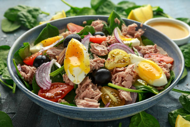 Protein packed tuna and soft, runny egg salad with pear shaped cherry tomatoes, black olives and spinach stock photo