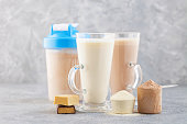 Sports nutrition, fitness diet and food concept - glass, protein shake bottle, powder and bars on grey background